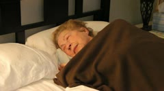 Elderly woman tossing and turning in bed Stock Footage