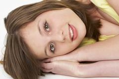 Young Girl Lying On Stomach In Studio Stock Photos