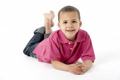 Young Boy Lying On Stomach In Studio - stock photo
