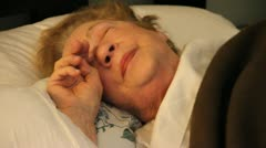 Elderly woman in bed wakes up, stretches and yawns - stock footage