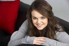 Teenage Girl Sitting On Sofa Stock Photos