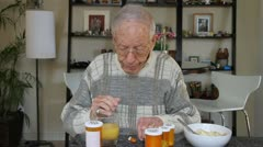 Elderly man taking medication Stock Footage