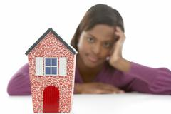 Stock Photo of Woman Looking At Model House