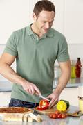 Man Preparing Meal In Kitchen - stock photo