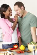 Young Couple Preparing Meal In Kitchen Stock Photos