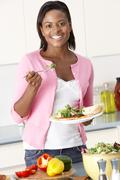 Woman Eating Meal In Kitchen Stock Photos