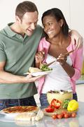 Young Couple Eating Meal In Kitchen Stock Photos