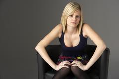 Studio Portrait Of Teenage Girl Sitting In Chair - stock photo
