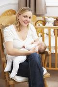 Mother Breastfeeding Baby In Nursery - stock photo