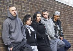 Gang Of Youths Leaning On Wall Stock Photos