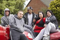 Gang Of Youths Sitting On Cars - stock photo