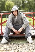 Young Man Sitting In Playground - stock photo
