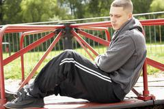Young Man Sitting In Playground Stock Photos