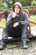 Young Man Sitting In Playground Smoking Joint - stock photo