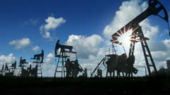 Working oil pumps silhouette against timelapse clouds Stock Footage
