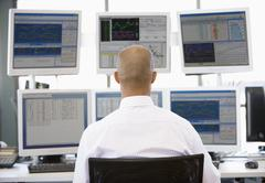 Stock Trader Looking At Multiple Monitors Stock Photos