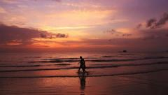 Mother and the son go on the seashore on a sunset. Stock Footage