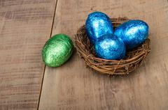 small bird's nest with four foil eggs - stock photo