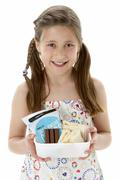 Studio Portrait of Smiling Girl Holding Lunchbox - stock photo