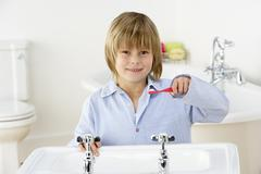 Young Boy Brushing Teeth at Sink - stock photo
