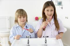 Siblings Brushing Teeth Together at Sink Stock Photos