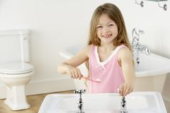 Young Girl Brushing Teeth at Sink - stock photo