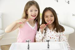 Two Young Girls Brushing Teeth at Sink - stock photo