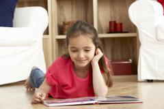 Young Girl Reading Book at Home Stock Photos