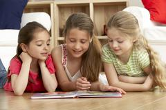 Three Young Girls Reading Book at Home Stock Photos