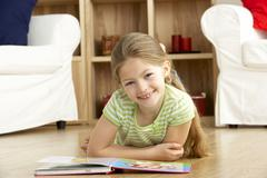 Young Girl Reading Book at Home Stock Photos