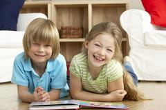 Two Young Children Reading Book at Home Stock Photos