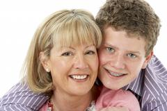 Studio Portrait of Smiling Teenage Boy with Mum Stock Photos