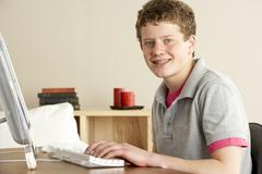 Smiling Teenage Boy Studying at Home - stock photo