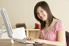 Smiling Teenage Girl on Computer at Home - stock photo