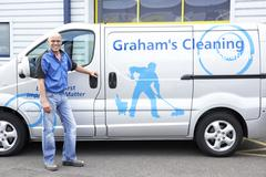 Cleaner standing next to van - stock photo