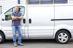 Man standing next to van - stock photo