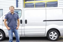 Stock Photo of Man standing next to van