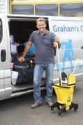 Stock Photo of Cleaner standing next to van