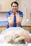 Osteopath treating female client - stock photo