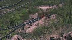 Mounted riders on dirt road framed by cactus Stock Footage