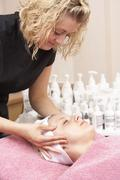 Female masseuse giving client facial - stock photo