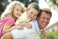 Father giving children piggyback Stock Photos
