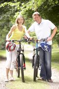 Couple riding bikes in countryside - stock photo