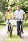 Stock Photo of Couple riding bikes in countryside