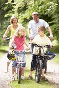 Family riding bikes in countryside Stock Photos