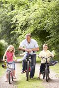 Father and children riding bikes in countryside - stock photo