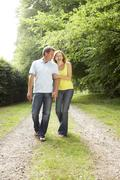 Middle aged couple walking in countryside Stock Photos