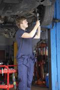 Mechanic working on car - stock photo