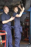 Mechanic and apprentice working on car Stock Photos