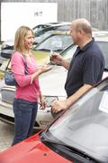 Stock Photo of Young woman collecting new car